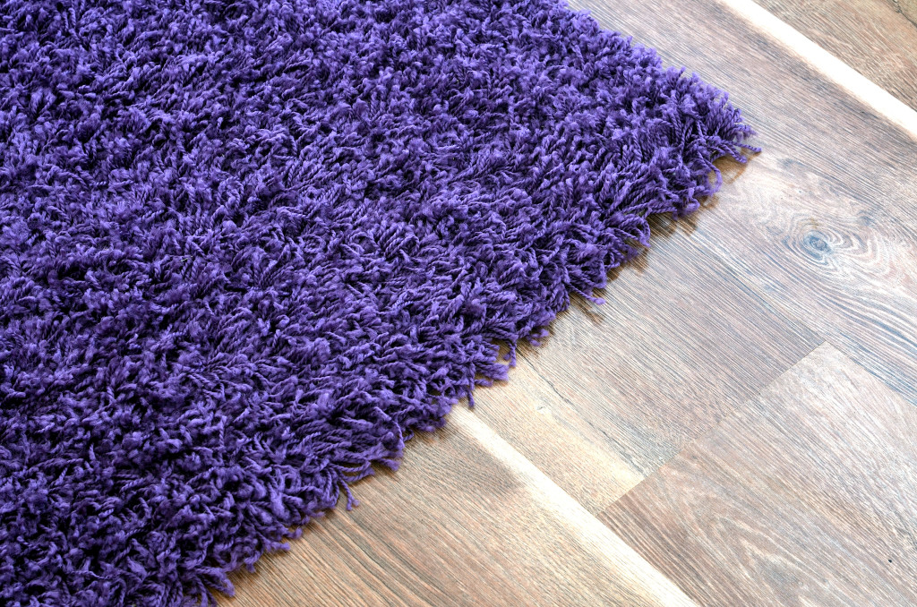 Purple shaggy carpet on brown wooden floor detail