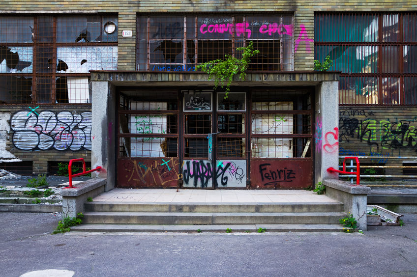 56389400 - entrance of an abandoned building covered in colorful graffiti