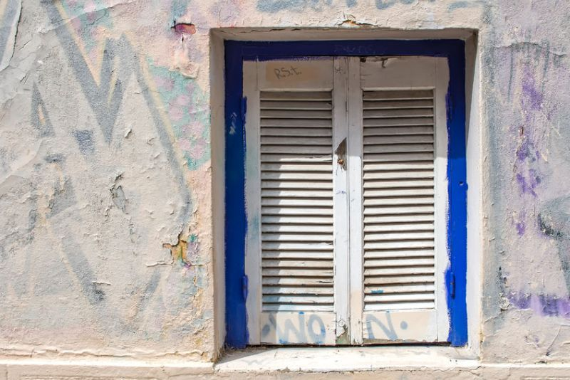 54216496 - blue framed window with white closed shutter. wall of the house with partly covered graffiti. plaka, athens, greece.