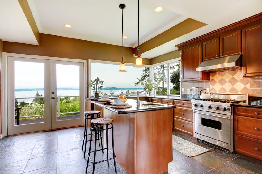 13888935 - luxury kitchen interior with green walls and stone floor and water view.