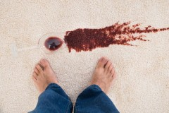37025087 - close-up of a person's feet standing near red wine spilled on carpet