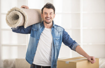 38295256 - the young happy man keeping carpet. moving, purchase of new habitation.