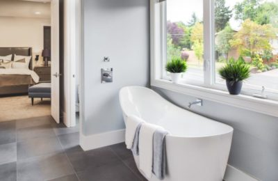 47256462 - bathtub in master bathroom in new luxury home with view of master bedroom and neighborhood with trees  through window